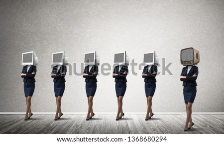 Business women in suits with monitors instead of their heads keeping arms crossed while standing in a row and one at the head with old TV in empty room against gray wall on background. #1368680294