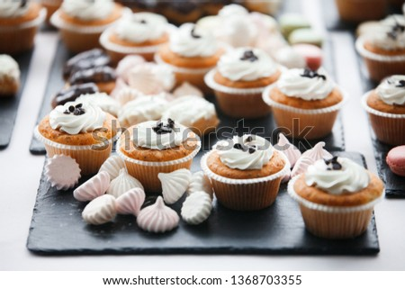 Beautiful multicolored decorated candy table baked sweet tasty cupcake cupcakes on a party, beautifully decorated catering banquet table with different candy sweet delicacy. #1368703355