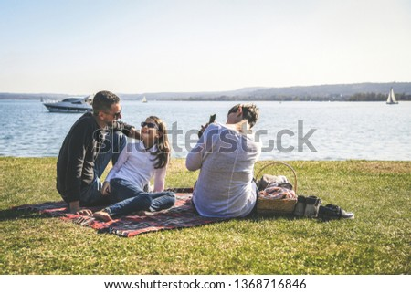 Portrait of mum and dad with little daughter celebrating birthday Pic-nic, snack with blanket on the lawn by the lake, joy in the family Concept of love for children free time spent with loved ones