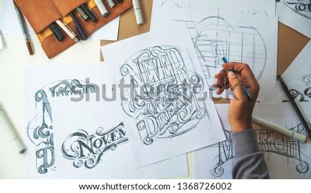 Typography Calligraphy artist designer drawing sketch writes letting spelled pen brush ink paper table artwork.Workplace design studio. #1368726002