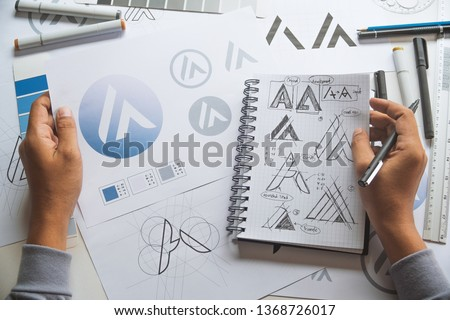 Graphic designer drawing sketch design creative Ideas draft Logo product trademark label brand artwork. Graphic designer studio Concept. #1368726017