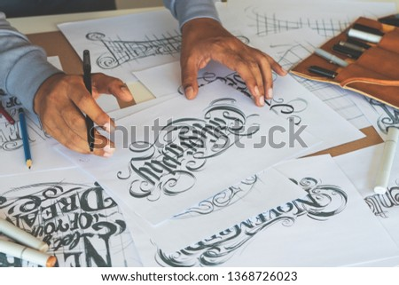 Typography Calligraphy artist designer drawing sketch writes letting spelled pen brush ink paper table artwork.Workplace design studio. #1368726023