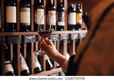 Bartender or male cavist standing near the shelves of wine bottles holds a glass of wine, looks at tint and smells flavor of wine in glass. #1368755939