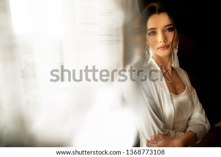 Bride in beautiful dress sitting on chair indoors in white studio interior like at home. Trendy wedding style shot. #1368773108