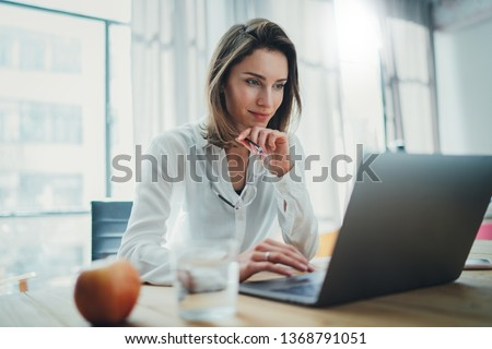 Confident businesswoman working on laptop at her workplace at modern office.Blurred background #1368791051