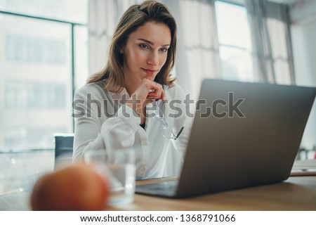 Handsome businesswoman working on laptop at her workplace at modern office.Blurred background #1368791066