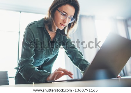 Portrait of Young handsome businesswoman using laptop computer at modern office.Blurred background #1368791165