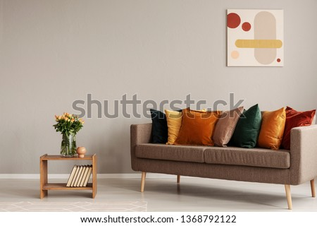 Roses in glass vase on wooden shelf with books next to comfortable sofa with orange, yellow, beige and emerald green pillows #1368792122
