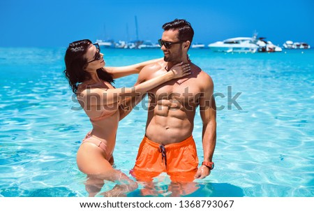Portrait of a sensual, young couple posing in a clear, tropical water #1368793067