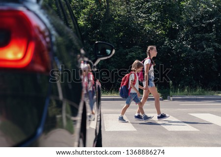 Children next to a car walking through pedestrian crossing to the school #1368886274