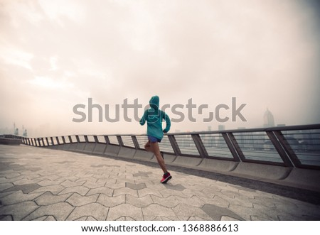Healthy lifestyle woman runner running on foggy city morning #1368886613