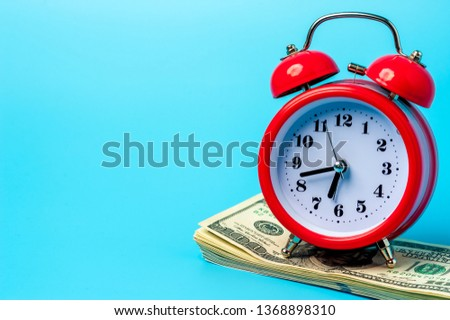 Time to make money concept, Red retro styled alarm clock on heap of american dollars. Banking, Savings, Wealth. #1368898310