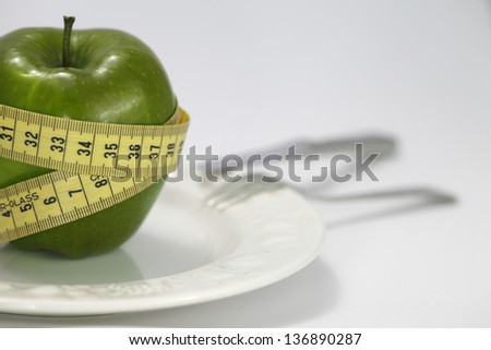 Green apple with measuring tape around on table #136890287