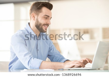 Young smiling broker in blue shirt typing on laptop keypad and looking at display while analyzing online data #1368926696