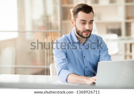 Serious young employee looking at laptop display while sitting by desk and analyzing online data #1368926711