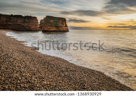 Sunrise over Ladram Bay on the Jurassic Coast World Heritage Site in East Devon, South West England, United Kingdom. Royalty-Free Stock Photo #1368930929