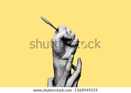 Concept of freedom of speech and information, stop censorship. Hand holding an open pen. It is dragged down by another hand. Black and white subject with a yellow background #1368949259