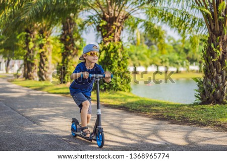 Child on kick scooter in park. Kids learn to skate roller board. Little boy skating on sunny summer day. Outdoor activity for children on safe residential street. Active sport for preschool kid #1368965774