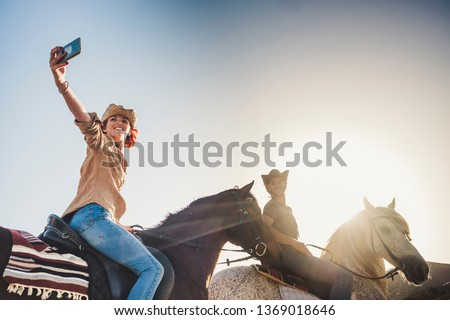 Happy couple on vacation take picture selfie with smart phone during a ride with horses in outdoor leisure activity together - clear sky and sunset light for free people