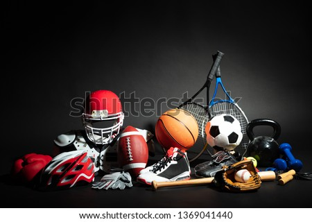 Variety Of Sport Balls And Equipment In Front Of Black Surface #1369041440