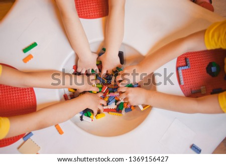 Top view of the hands of little girls playing with toy bricks on the table in kindergarten #1369156427