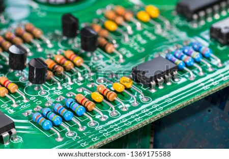 Electronic components. Integrated circuits, resistors, transistors and capacitors on PCB. Green copper board detail. Standard color code. Old computer hardware. Electrotechnology. Waste sorting. Eco. #1369175588