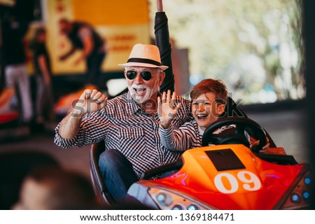 Grandfather and grandson having fun and spending good quality time together in amusement park. They enjoying and smiling while driving bumper car together. #1369184471