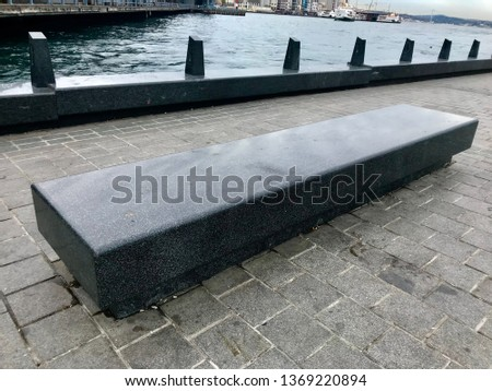 Grey large seat bench stands on the stone floor is a great background #1369220894