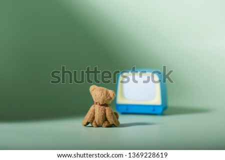 miniature szene back view cute brown Teddy bear sitting on floor watching a retro style empty TV screen with green backround. concept of neglecting analog toys for digital communication media.  #1369228619