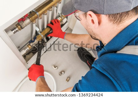 Plumbing System Fix Job. Caucasian Technician Looking For Potential Issue Inside Residential Central Heating System. #1369234424