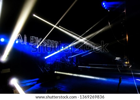 ODESSA, UKRAINE - Apr 12, 2019: Stage lighting. Projectors in dark. Multicolored light rays from stage spotlights on stage in smoke during an entertainment show. Night club. Lights show. Laser show #1369269836