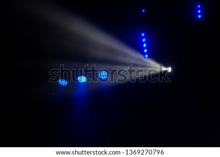 Stage lights. Several projectors in the dark. Multi-colored light beams from the stage spotlights on the stage in the smoke at the time of the entertainment show. Night club. Lights show. Lazer show #1369270796