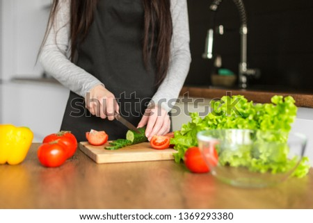 Young trendy woman cooking healthy food in the morning #1369293380