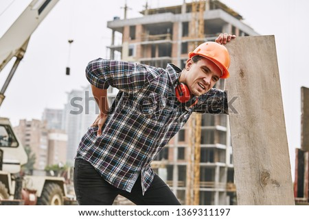 Hard work. Construction worker in protective helmet feeling back pain while working at construction site. Building construction. Pain concept #1369311197