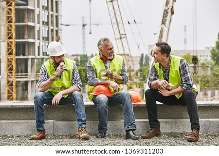 Time for a break. Group of builders in working uniform are eating sandwiches and talking while sitting on stone surface against construction site. Building concept. Lunch concept #1369311203