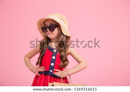 little fashionista with a shopping bag in summer hat and sunglasses , colorful pink background , the concept of children's fashion #1369316615