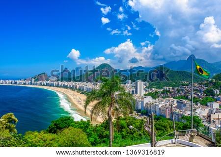 Copacabana beach in Rio de Janeiro, Brazil. Copacabana beach is the most famous beach of Rio de Janeiro, Brazil. Skyline of Rio de Janeiro with flag of Brazil Royalty-Free Stock Photo #1369316819
