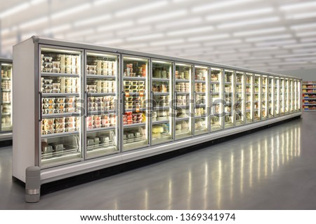 Ice cream and birthday cakes in a Big glass door deep freezer at supermarket. Suitable for presenting new ice cream, cakes and frozen product in between many others.  #1369341974