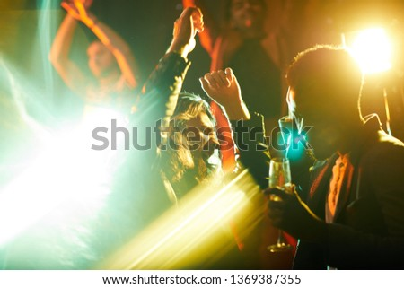 Emotional young bearded man with closed eyes dancing with raised hands and singing song at party in modern nightclub, defocused light effect #1369387355
