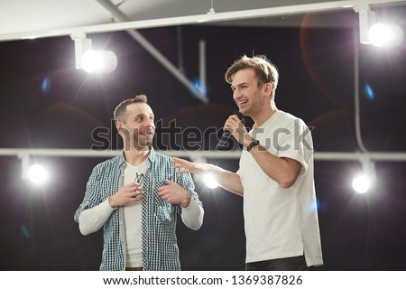 Waist up portrait of young show host presenting mature man standing on stage in spotlight, copy space