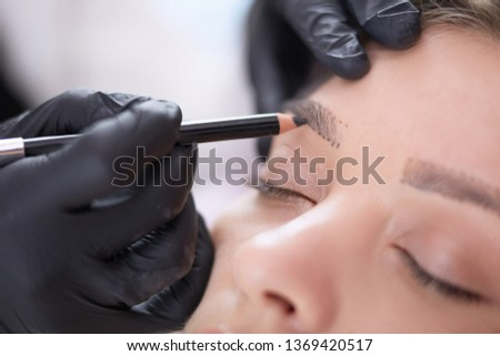 Cosmetologist applying permanent make up on eyebrows #1369420517