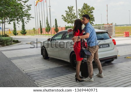 Sepang, Malaysia - March 28th, 2019 : Flight attendant with her husband at  airport. Working travel concept with women on professional uniform at departure terminal gate ready for boarding . #1369440971
