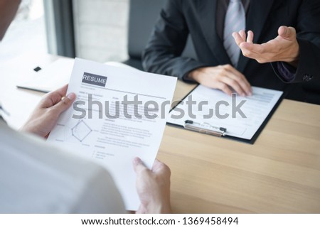 Employer or recruiter holding reading a resume during about colloquy his profile of candidate, employer in suit is conducting a job interview, manager resource employment and recruitment concept. #1369458494