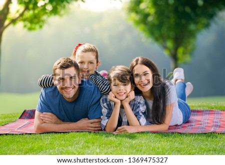 Color photo of smiling young parents and two children, lying together on a picnic blanket, outdoor. Love, family and happy childhood lifestyle concept.