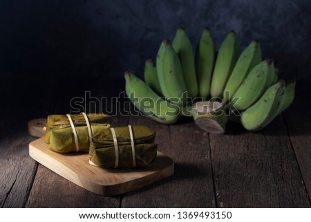 A pair of rice porridge is placed on a wooden cutting board, which is made from sticky rice, banana, black beans, coconut milk and sugar. #1369493150