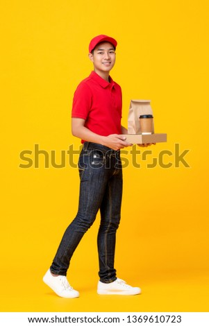 Young Asian male fast food crew in red uniform delivering take away meal in yellow isolated studio background #1369610723