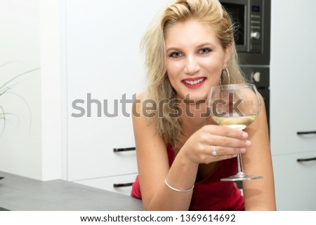 a beautiful young blonde woman with red dress drinking white wine #1369614692