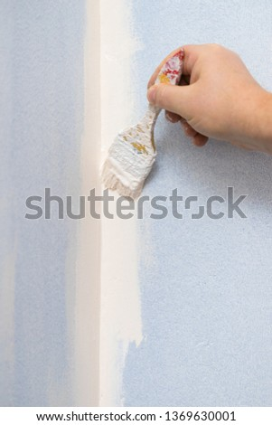 Person appplying white paint on blue wall using brush. Home renovation concept. #1369630001