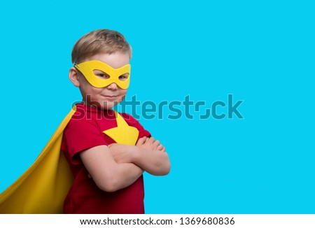 Little child superhero with yellow cloak and star. Happy smiling kid in glasses ready for education. Success, motivation concept. Back to school. Little businessman isolated on blue, Boy superhero.  #1369680836