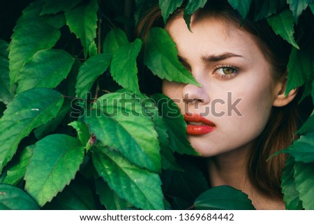 woman hid in the bushes a beautiful face bright makeup                      #1369684442
